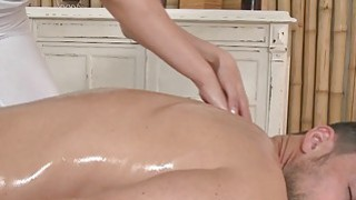 Sexy masseuse oils and  wanks cock in massage room